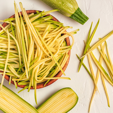 Raw zucchini pasta on white background, copy space, top view. Stock Photo