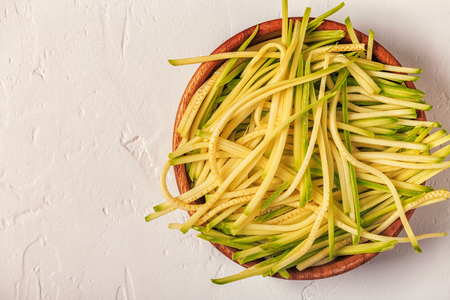 spiralized: Raw zucchini pasta on white background, copy space, top view. Stock Photo