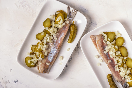Traditional Dutch raw herring with onions and pickles on white background. Reklamní fotografie