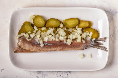 Traditional Dutch raw herring with onions and pickles on white background. Banco de Imagens