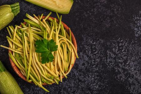 healty: Raw zucchini pasta on dark background, copy space, top view.