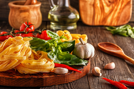 Products for cooking - pasta, tomatoes, garlic, pepper, and basil on the old wooden background. Фото со стока