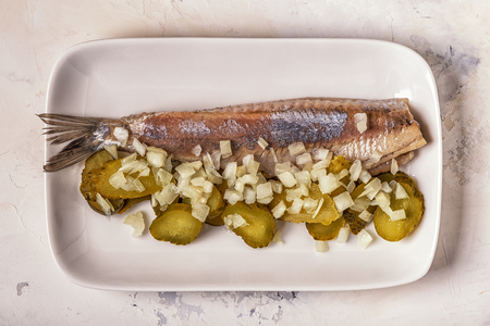 Traditional Dutch raw herring with onions and pickles on white background. Stockfoto