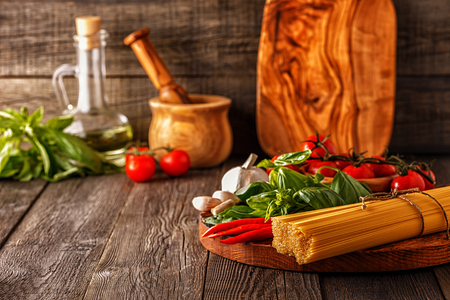 Products for cooking - pasta, tomatoes, garlic, pepper, and basil on the old wooden background. Standard-Bild