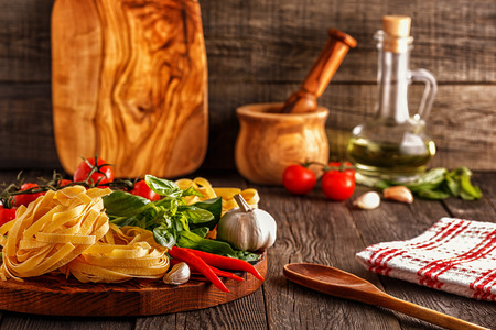 Products for cooking - pasta, tomatoes, garlic, pepper, and basil on the old wooden background. Stock Photo
