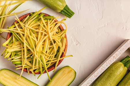 healty: Raw zucchini pasta on white background, copy space, top view. Stock Photo