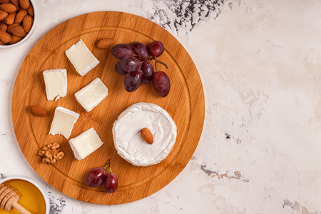 Dish with  cheese, grapes, nuts and honey. Top view.