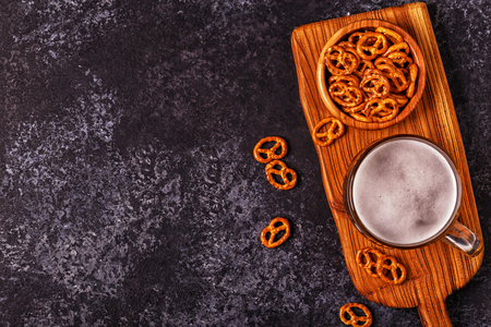 Beer and salted pretzel  on stone background. Top view, copy space.