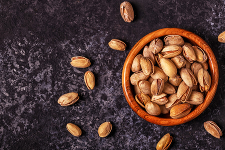 Salted pistachios in a bowl on stone background. Top view, copy space. Imagens