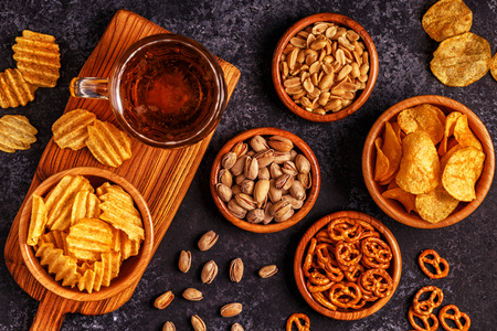 pretzel: Beer with snacks on stone background. Top view, copy space. Stock Photo