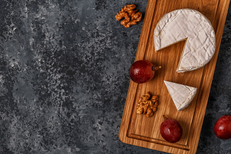 Camembert cheese on cutting board, top view, copy spase.