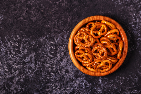 Salted pretzel in a bowl on stone background. Top view, copy space.