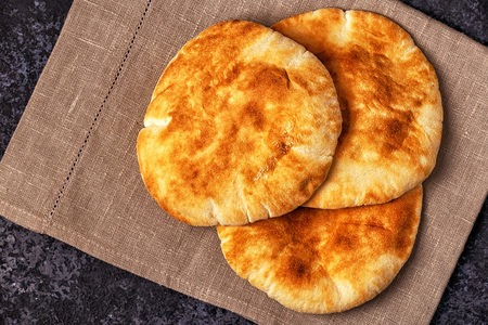 Pita bread on a dark table, top view, copy space. Stock Photo
