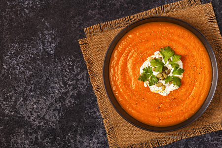 Pumpkin and carrot soup with cream, seeds and parsley. Top view.
