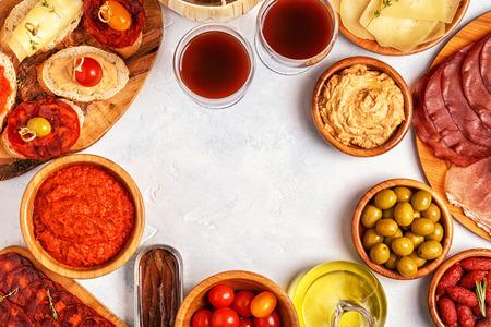 Conceito típico de tapas espanholas. O conceito inclui fatias de jamon, chouriço, salsicha, bacias com azeitonas, tomates, anchovas, grão-de-bico e queijo. Foto de archivo - 86058247