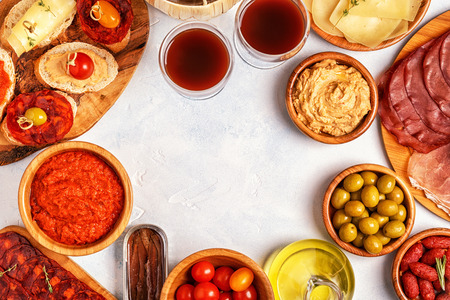 Typical spanish tapas concept. Concept include slices jamon, chorizo, sausage, bowls with olives, tomatoes, anchovies,  mashed chickpeas, cheese. Banco de Imagens