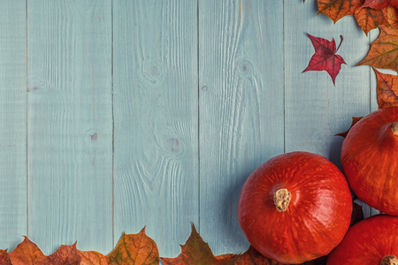 Autumn background with colored leaves and pumpkins on wooden background. Top view with copy space.