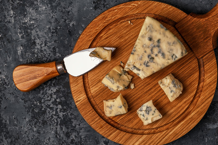 Pieces of blue cheese on wooden serving board, top view. Reklamní fotografie