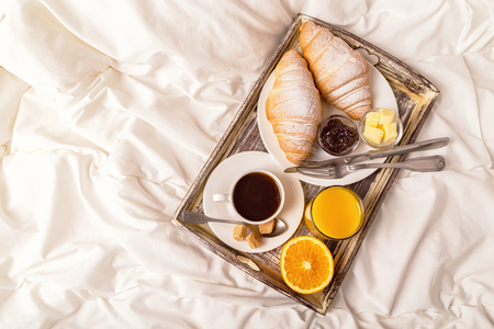 Delicious breakfast in bed with coffee and croissants.