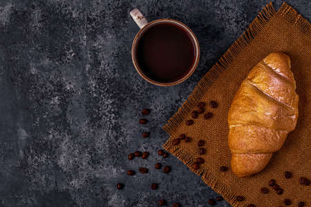 Fresh croissant on dark background. Top view, copy space.