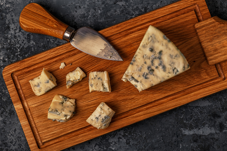 Pieces of blue cheese on wooden serving board, top view. Stock fotó