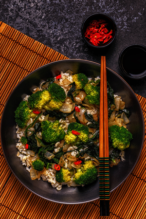 Cooking asian stir fry rice with vegetables, top view, copy space.