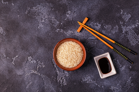 Rice in a bowl and wooden chopsticks. Top view, copy space.
