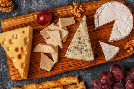 Assorted cheeses on wooden board, top view, copy space. Фото со стока