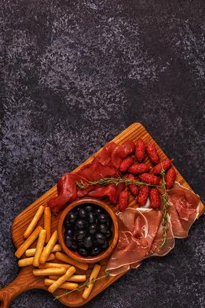 Sausage olives prosciutto breadsticks wine.