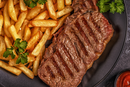 Beef barbecue steak with french fries, top view. Stock Photo