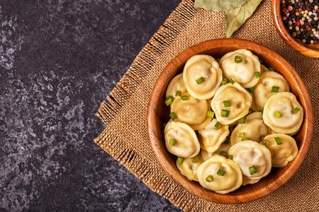 Homemade meat dumplings - russian pelmeni. Top view, copy space.