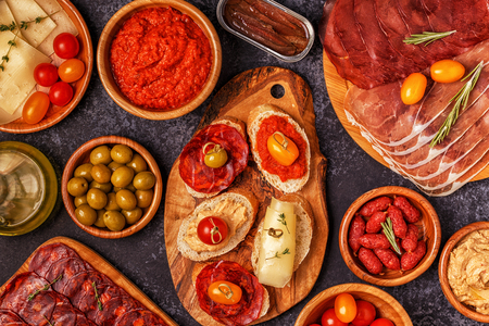 Concepto típico de tapas españolas. El concepto incluye rebanadas de jamón, chorizo, salchichas, tazones con aceitunas, tomates, anchoas, puré de garbanzos, queso. Foto de archivo - 89790535