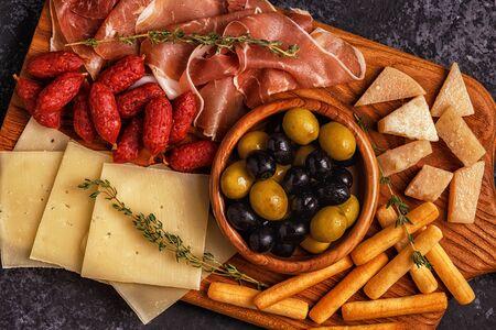 Sausage olives prosciutto cheese bread sticks wine. Stock Photo
