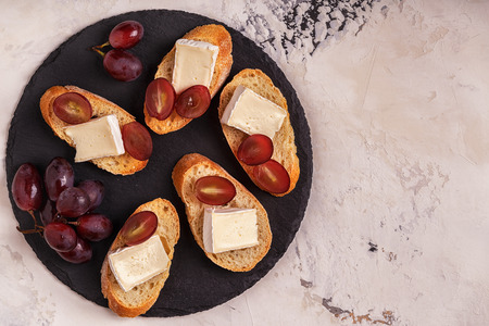 Dish with sandwiches of cheese, grapes and honey. Top view. Stock Photo