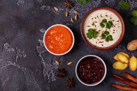 Traditional Indian raita with cucumber, cumin, coriander and chutney sauces. Top view, copy space. Stock Photo