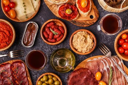 Concepto típico de tapas españolas. El concepto incluye rebanadas de jamón, chorizo, salchichas, tazones con aceitunas, tomates, anchoas, puré de garbanzos, queso. Foto de archivo - 91284074