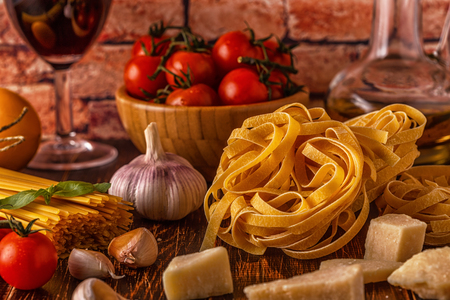 Products for cooking - pasta, tomatoes, garlic, olive oil and red wine. Selective focus. Stock Photo