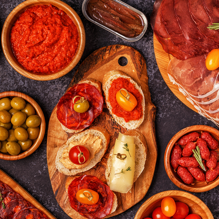 Typical spanish tapas concept. Concept include slices jamon, chorizo, sausage, bowls with olives, tomatoes, anchovies,  mashed chickpeas, cheese. Stock Photo