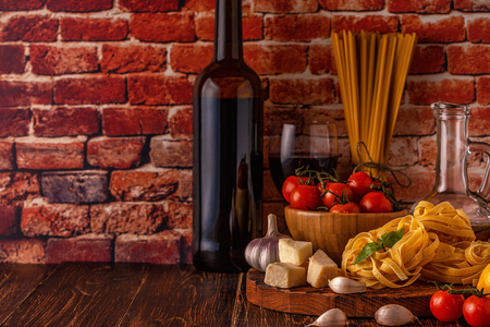 Products for cooking - pasta, tomatoes, garlic, olive oil and red wine. Selective focus. Фото со стока