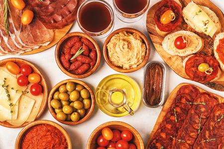 Concepto típico de tapas españolas. El concepto incluye rebanadas de jamón, chorizo, salchichas, tazones con aceitunas, tomates, anchoas, puré de garbanzos, queso. Foto de archivo - 91284177