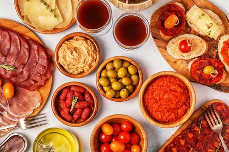Concepto típico de tapas españolas. El concepto incluye rebanadas de jamón, chorizo, salchichas, tazones con aceitunas, tomates, anchoas, puré de garbanzos, queso. Foto de archivo - 91284182