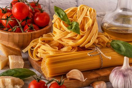 調理のための製品 - パスタ、トマト、ニンニク、オリーブオイル、バジル。選択的な焦点。 写真素材