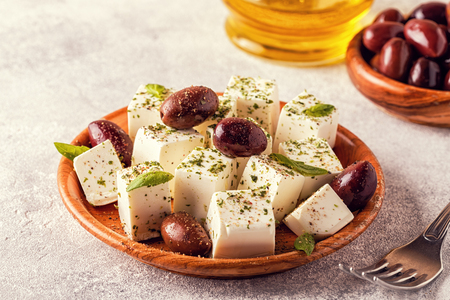 Greek cheese feta with oregano and olives, selective focus.
