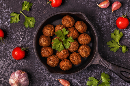 Roasted  meatballs with tomatoes, garlic and parsley. Top view, copy space. Stock Photo - 91693557