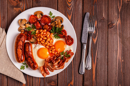 Traditional full English breakfast with fried eggs, sausages, beans, mushrooms, grilled tomatoes and bacon on wooden background. Top view Stock Photo