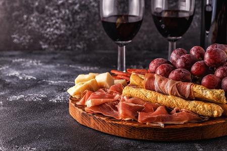 Prosciutto, sausage, wine, grape, parmesan on dark table, selective focus.