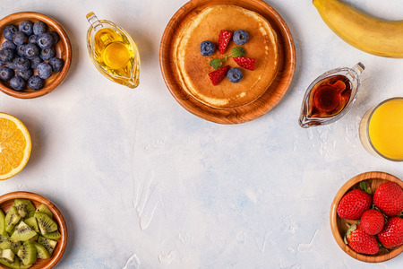 Pancakes with fruit, honey, maple syrup. Top view.