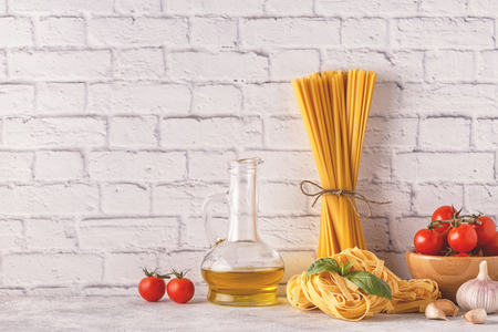 Products for cooking - pasta, tomatoes, garlic, olive oil, basil. Selective focus.