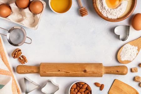 Ingredienti per la cottura - farina, cucchiaio di legno, mattarello, uova. Vista dall'alto, copia spazio. Archivio Fotografico