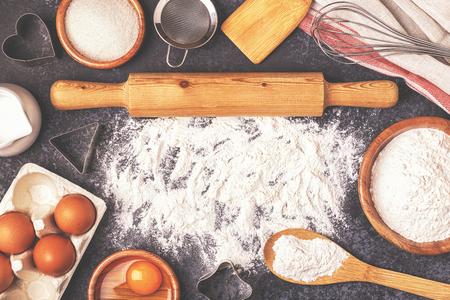 Ingredienti per la cottura - farina, cucchiaio di legno, mattarello, uova. Vista dall'alto, copia spazio.